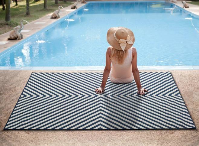 Nuestra alfombra para exteriores e interiores CALA 13. Alfombra fina con estampado geométrico en blanco y azul.